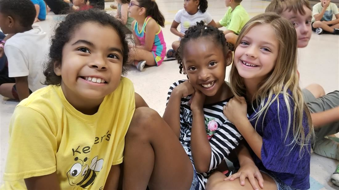 Three girls sitting on the floor at summer camp