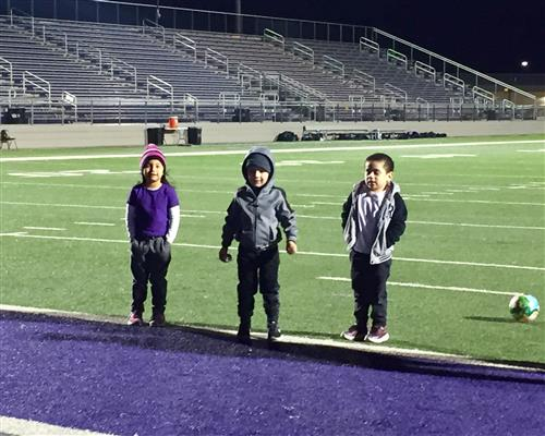 Pre-K students shooting goals at halftime soccer game