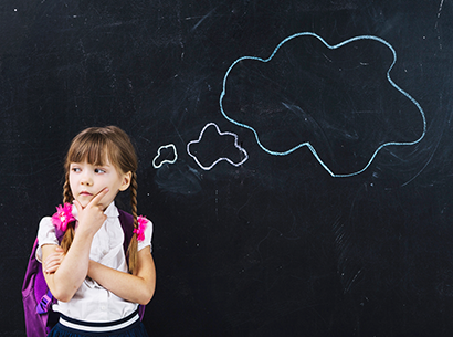 Little girl thinking in front of a blackboard with an image of a lightbulb drawn in chalk