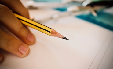 Student holding a sharpened pencil, ready to write